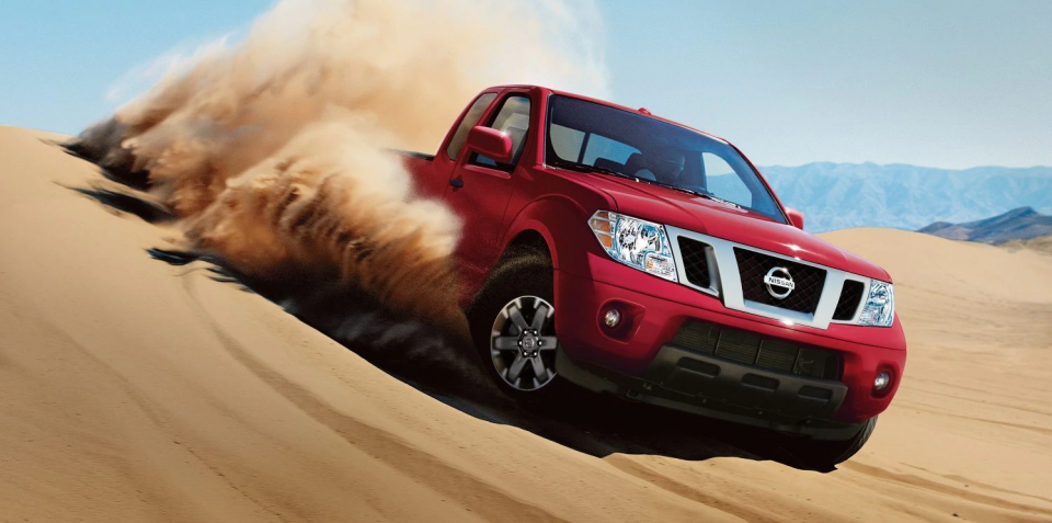 A red 2020 Nissan Frontier pickup truck coasting down a sand dune.