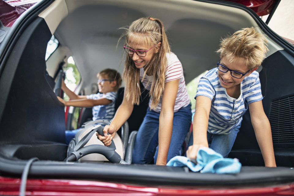 Kids cleaning the interior of the family car