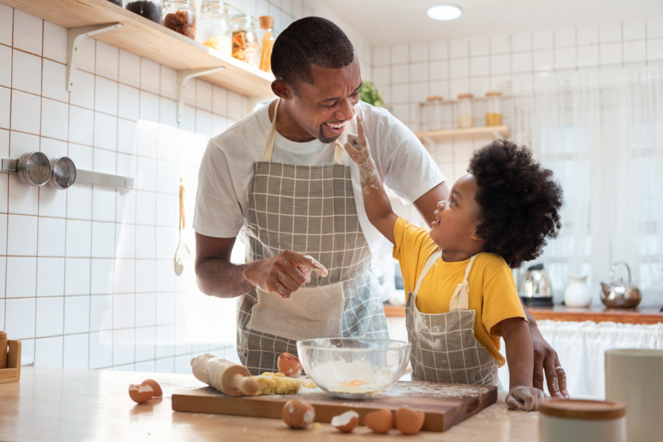 Father and son have fun baking in the kitchen together.