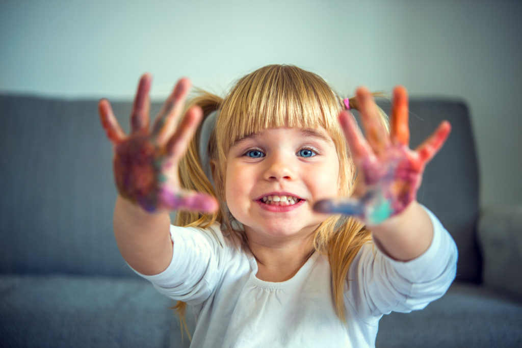 Young girl smiling with paint on her hands