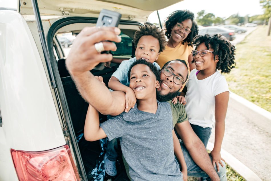 Family excited and taking selfie before road trip
