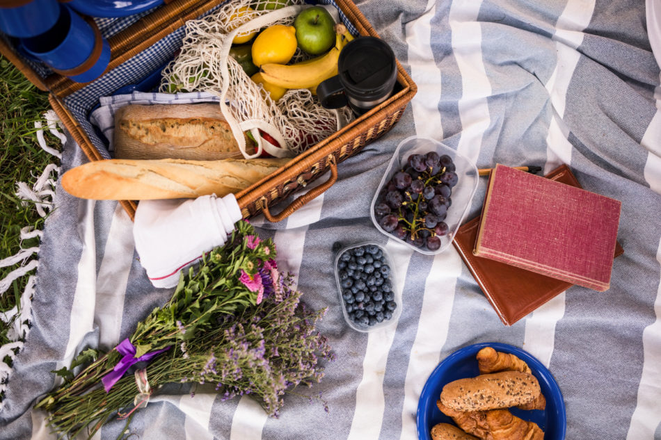 picnic blanket on the grass with flowers, fruits and bread to share. Books are also placed for people to read them