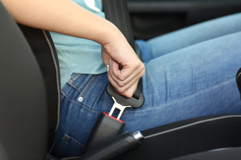 Driver hand fastening seatbelt in a car